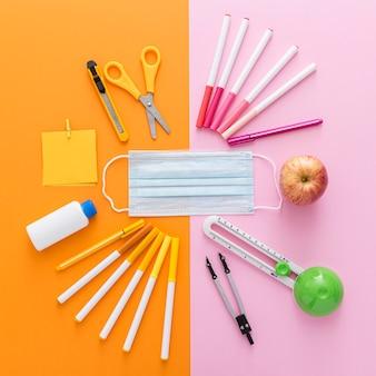 Vue de dessus des fournitures scolaires avec masque médical et crayons