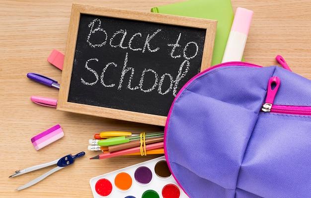 Vue de dessus des fournitures scolaires avec sac à dos et tableau noir