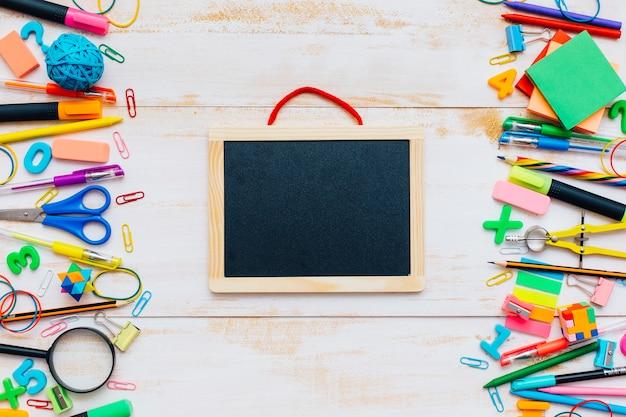 Vue de dessus des fournitures scolaires sur une table en bois blanc