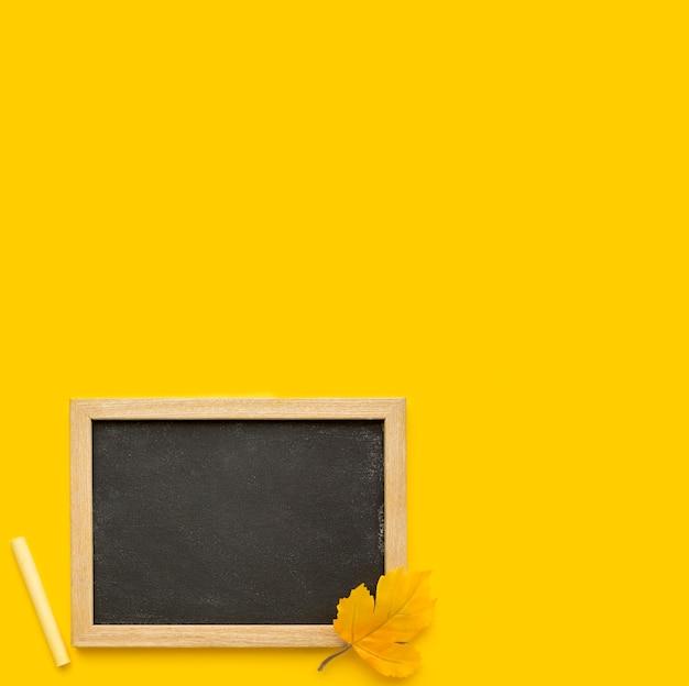 Vue de dessus des fournitures scolaires avec tableau noir et espace copie