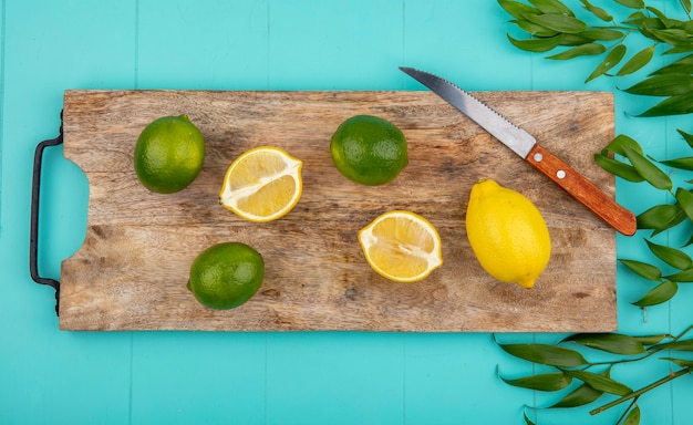 Vue de dessus de frais un citrons colorés sur une planche de cuisine en bois avec un couteau avec des feuilles sur bleu