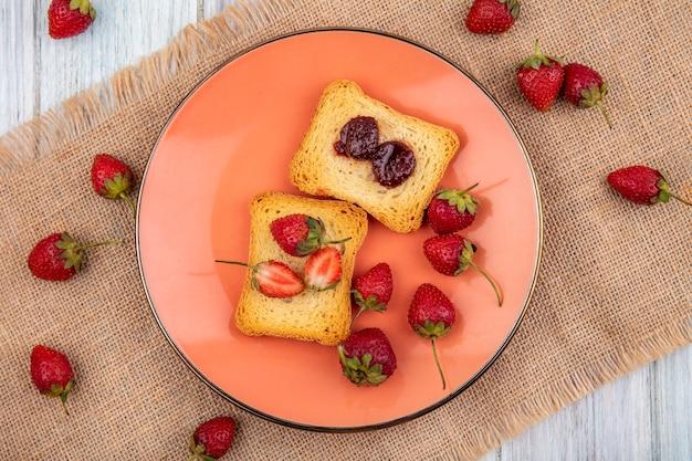 Vue de dessus de la fraise sur une assiette avec des fraises fraîches isolé sur un sac en tissu sur un fond en bois gris