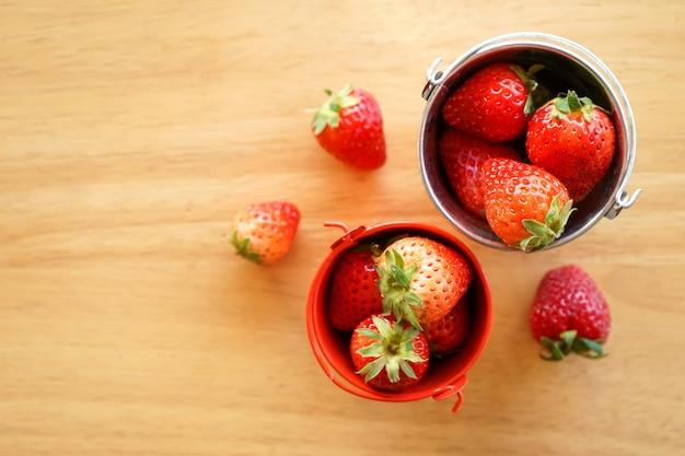Vue de dessus de fraise fraîche dans un petit seau d'eau en acier inoxydable sur un bureau en bois avec espace copie