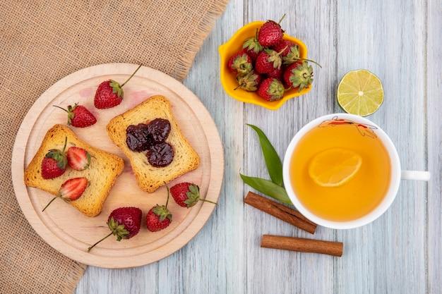 Vue de dessus de la fraise sur une planche de cuisine en bois sur tissu sac avec des bâtons de cannelle avec une tasse de thé sur un fond en bois gris