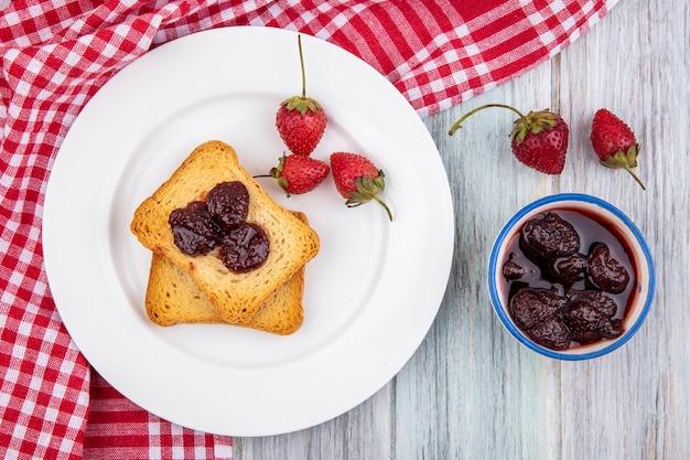 Vue de dessus de fraise sur une plaque blanche sur un tissu à carreaux rouge avec une confiture de fraises sur un bol sur un fond de bois gris