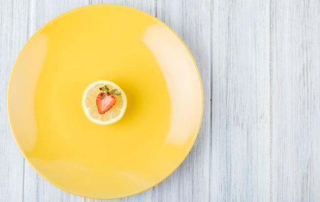 Vue de dessus de fraise avec une tranche de citron et copie espace sur fond de bois blanc