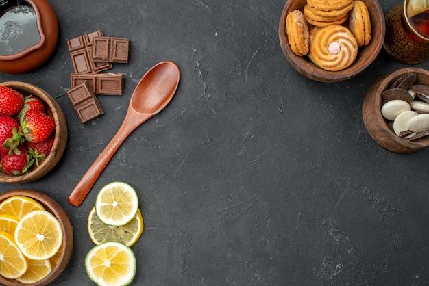 Vue de dessus fraises et citrons de fruits frais avec des biscuits sur une surface grise