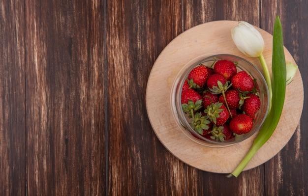 Vue de dessus des fraises dans un bol et fleur sur une planche à découper sur fond en bois avec espace copie