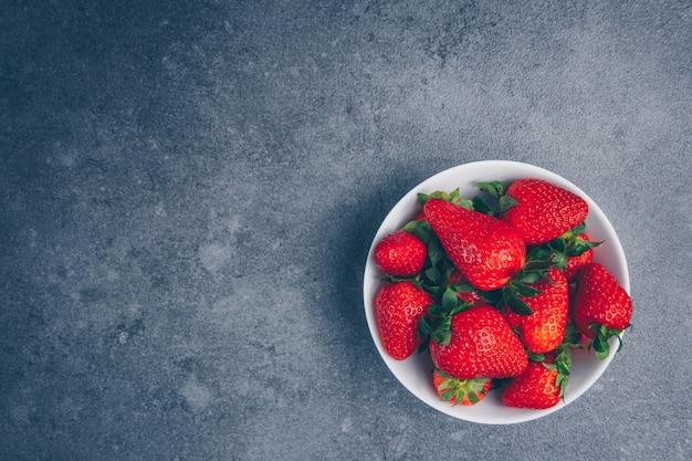 Vue de dessus des fraises dans un bol sur fond texturé gris. espace horizontal pour le texte