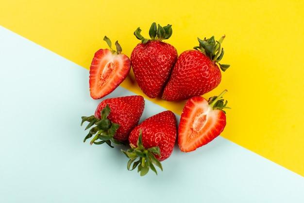 Vue de dessus de fraises entières en tranches moelleux juteux sur le plancher bleu-jaune