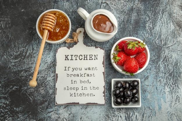 Vue de dessus des fraises fraîches avec un bureau drôle et du miel sur la surface sombre des baies de fruits sucrés