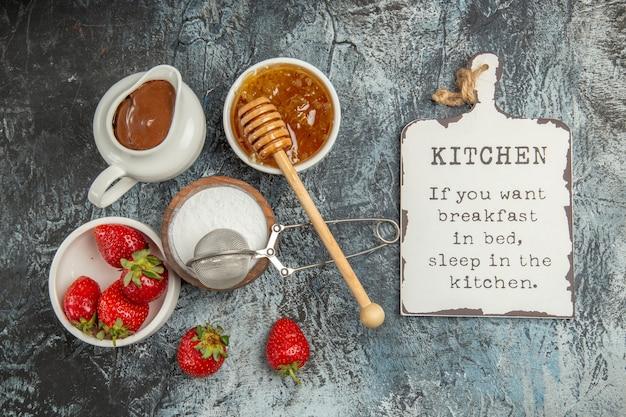 Vue de dessus fraises fraîches avec du miel sur la surface sombre fruits baies sucrées