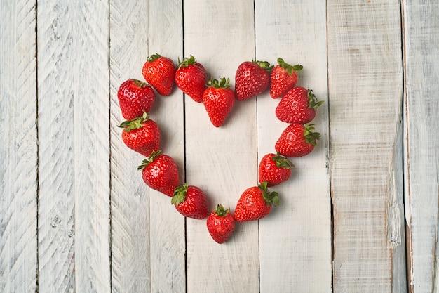 Vue de dessus des fraises rouges formant un coeur sur une table en bois blanc. concept d'amour et de couple.