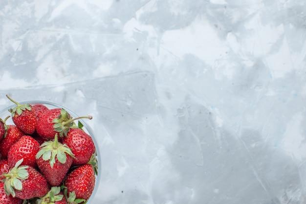 Vue de dessus des fraises rouges fraîches baies d'été moelleuses à l'intérieur de la plaque de verre sur un bureau léger, berry fruit mellow vitamine