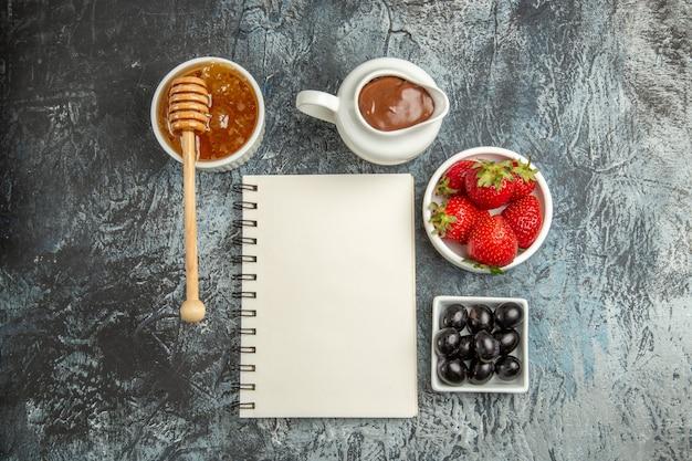 Vue de dessus fraises rouges fraîches avec du miel et des olives sur la couleur des fruits de surface légère