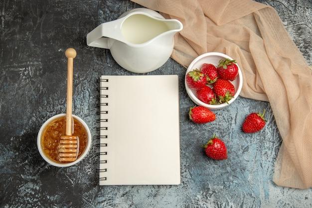 Vue de dessus fraises rouges fraîches avec du miel sur la surface sombre-lumière baies de fruits rouges