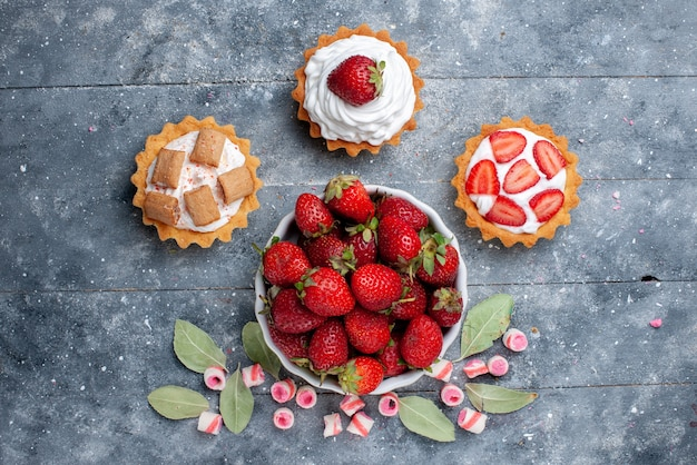 Vue de dessus de fraises rouges fraîches à l'intérieur de la plaque avec des bonbons et des gâteaux roses tranchés sur gris, baies de fruits frais moelleux