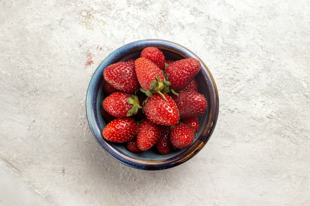 Vue de dessus fraises rouges fraîches à l'intérieur de la plaque sur l'espace blanc