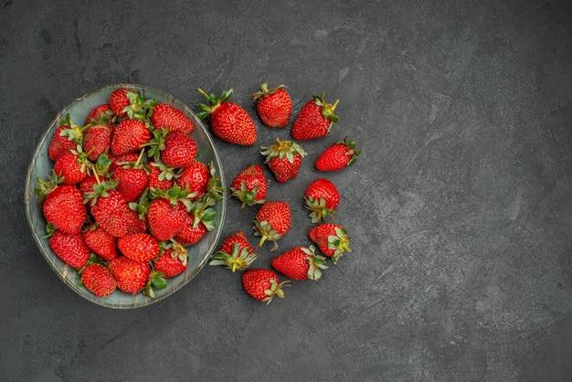 Vue de dessus fraises rouges fraîches à l'intérieur de la plaque sur fond gris