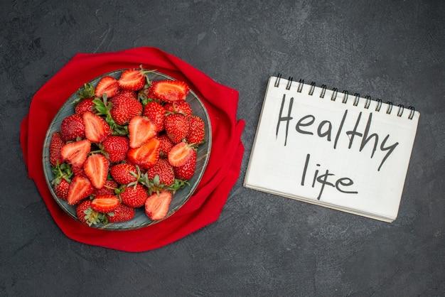 Vue de dessus des fraises rouges fraîches à l'intérieur de la plaque sur fond sombre