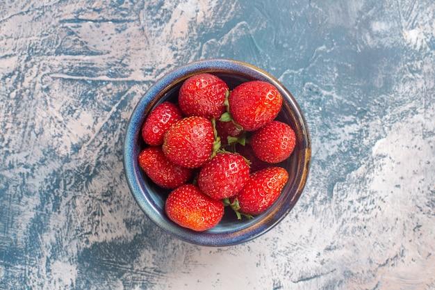 Vue de dessus des fraises rouges fraîches à l'intérieur de la plaque sur une surface légère