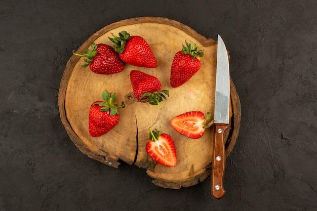 Vue de dessus des fraises rouges fraîches tranchées mûres sur le bureau brun foncé et
