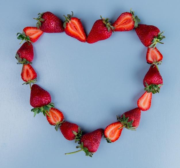 Vue de dessus des fraises sur la surface bleue avec le concept de coeur de l'espace de copie