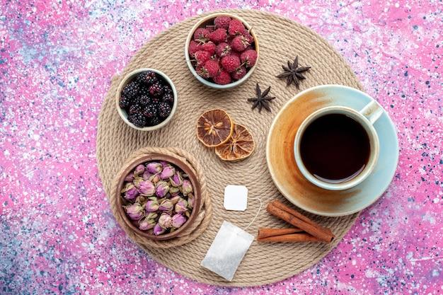 Vue de dessus framboises et mûres baies fraîches avec tasse de thé à la cannelle sur le bureau rose.