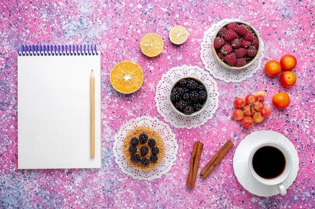 Vue de dessus framboises et mûres de baies sauvages fraîches avec petit gâteau et thé sur le bureau rose.