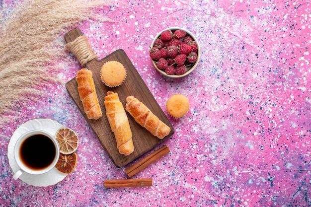 Vue de dessus de framboises savoureuses fraîches à l'intérieur de la plaque blanche avec des bagels de thé et de la cannelle sur la surface rose