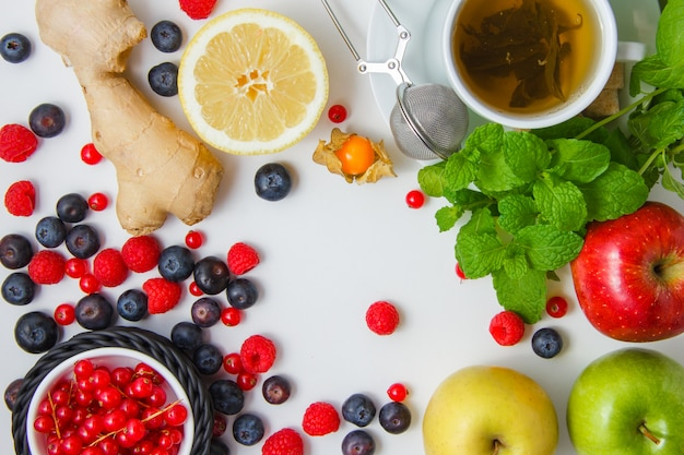 Vue de dessus framboises avec thé, pommes, bleuets, groseilles, citron, gingembre, feuilles de menthe sur une surface blanche. horizontal