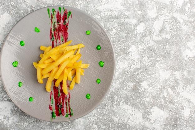 Vue de dessus des frites cuites et salées à l'intérieur de la plaque sur le bureau gris clair