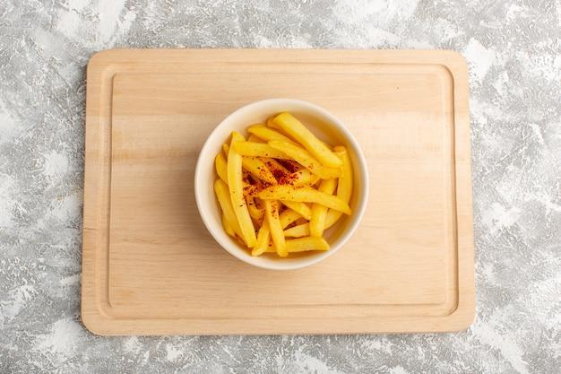 Vue de dessus des frites avec du poivre à l'intérieur de la plaque blanche