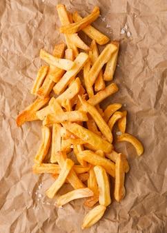 Vue de dessus des frites avec du sel sur papier