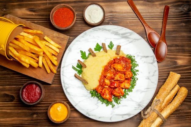 Vue de dessus des frites avec des tranches de poulet sur une table marron