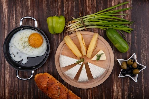 Vue de dessus fromage feta avec fromage fumé sur un support avec des olives poivrons verts concombre et oeufs sur un fond en bois