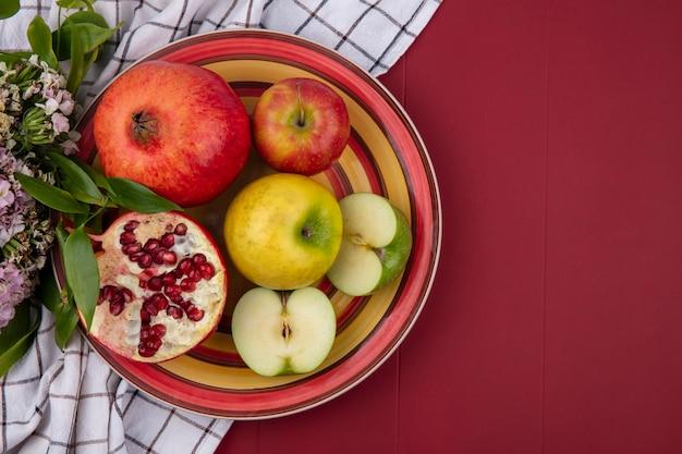 Vue de dessus des fruits en assiette et fleurs sur tissu à carreaux sur surface rouge