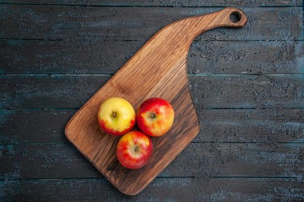 Vue de dessus des fruits à bord de trois pommes jaune-rougeâtre sur une planche à découper en bois sur une surface grise