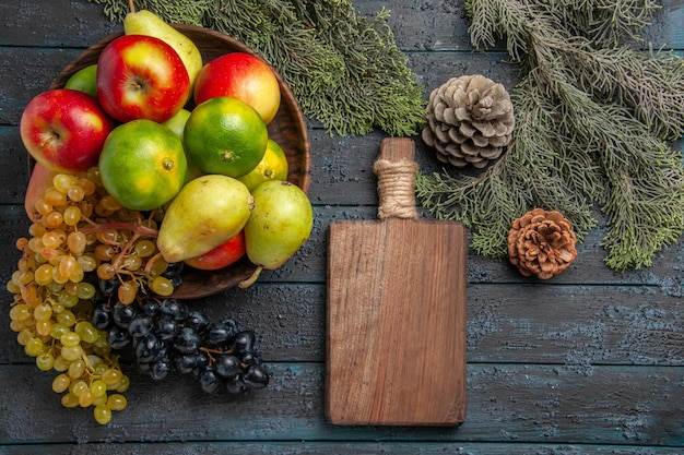 Vue de dessus fruits et branches raisins blancs et noirs citrons verts poires pommes dans un bol à côté de branches d'épinette planche à découper et cônes sur surface grise