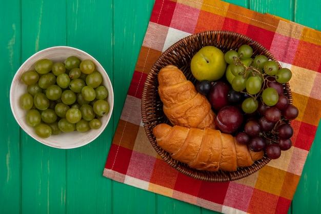Vue de dessus des fruits comme les baies de prunelle pluots de raisin avec des croissants dans le panier sur tissu à carreaux et bol de baies de raisin sur fond vert