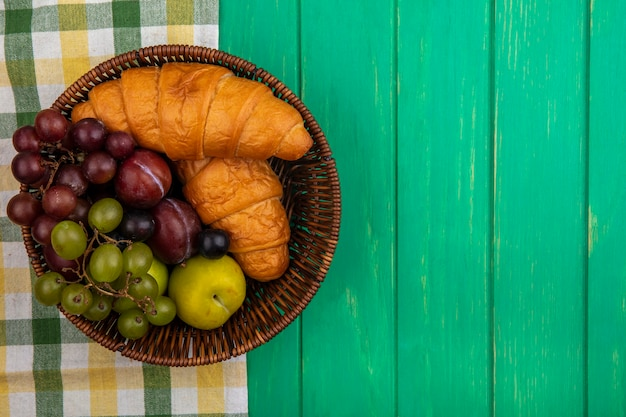 Vue de dessus des fruits comme les baies de prunelle de raisin pluots avec des croissants dans le panier sur tissu à carreaux et fond vert avec copie espace