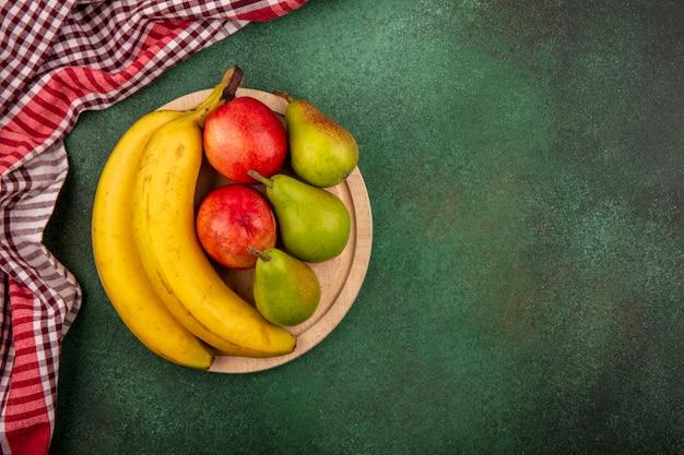 Vue de dessus des fruits comme banane poire pêche sur planche à découper avec un tissu à carreaux sur fond vert avec espace copie