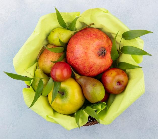 Vue de dessus des fruits comme la pêche prune pomme et la grenade dans le panier sur la surface blanche