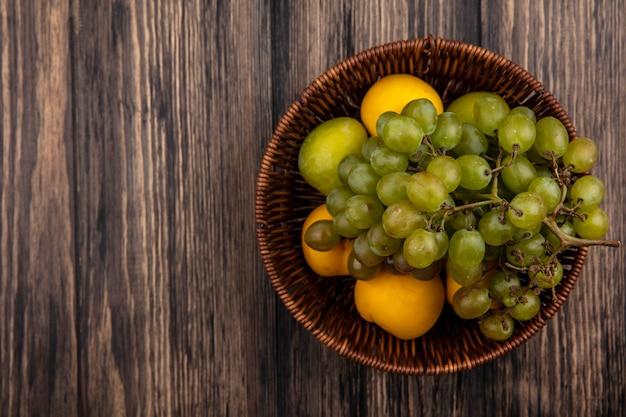 Vue de dessus des fruits comme pluot vert raisin et nectacots dans le panier sur fond de bois avec espace copie
