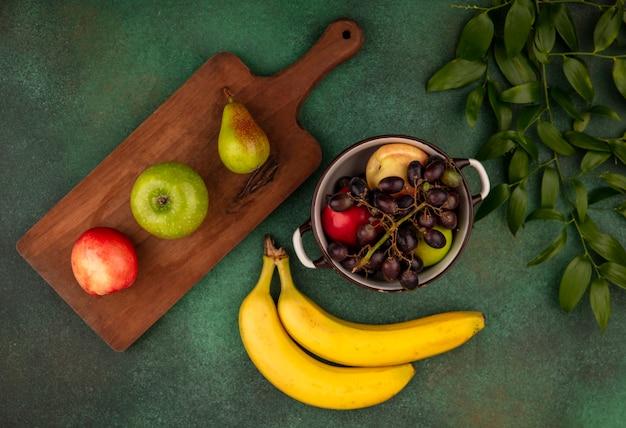 Vue de dessus des fruits comme poire pêche raisin en pot et sur une planche à découper avec des feuilles sur fond vert