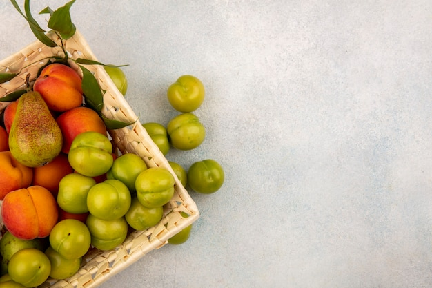 Vue de dessus des fruits comme la prune abricot poire dans le panier et sur fond blanc avec copie espace