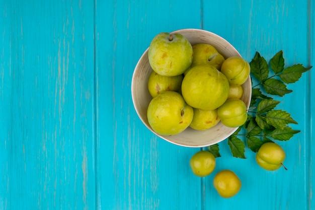 Vue de dessus des fruits comme les prunes et les pluots verts dans un bol avec des feuilles sur fond bleu avec copie espace