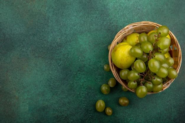 Vue de dessus des fruits comme raisin et pluot dans le panier sur fond vert avec espace copie