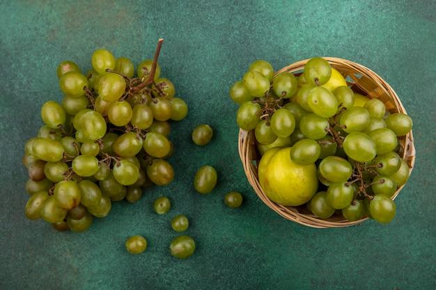 Vue de dessus des fruits comme raisin et pluot dans le panier et grappe de raisin sur fond vert
