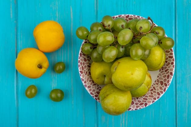 Vue de dessus des fruits comme le raisin et les pluots verts dans un bol avec des nectacots et des baies de raisin sur fond bleu